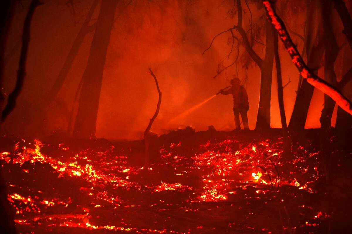 A firefighter sprays water on hot spots while battling the Glass Fire on Oct. 1, 2020, in Calistoga, Calif. The fast-moving Glass Incident Fire, originally called the Glass Fire, has burned 67,000 acres in Sonoma and Napa counties and has destroyed numerous wineries and structures.