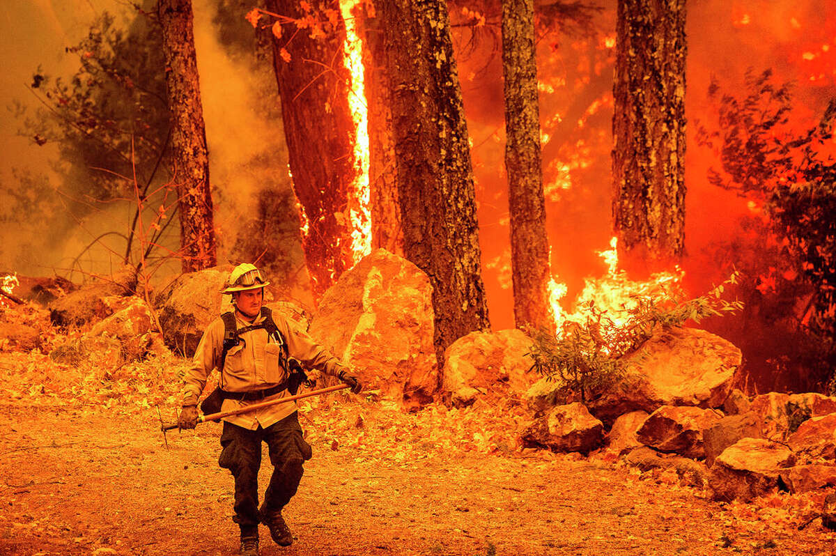 A firefighter walks a path as the Glass Fire burns along Highway 29 in Calistoga, Calif., on Thursday, Oct. 1, 2020.