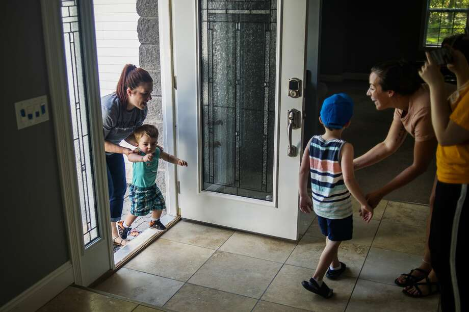 Lisa Homrich, left, ushers her sons, Truett, 1, and Brayden, 4, into the home the family will be staying in, thanks to Bruce and Robin Malone, Wednesday, May 27, 2020 in Midland. The Homrichs' home on Marvo Court was devastated by flooding. (Katy Kildee/kkildee@mdn.net) Photo: (Katy Kildee/kkildee@mdn.net)