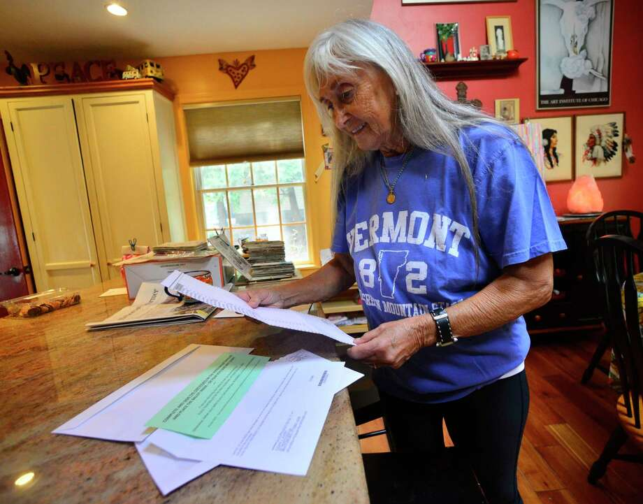 """Susan Avery, of Brattleboro, Vt., looks over her November election ballot that she received in the mail before filling it out on Monday, Sept. 28, 2020. At age 73, Avery said this is the first time that she can remember as an adult being interested in what's going on in the political scene. """"One must be blind to not see what's happening around us, and we need to make our voices heard,"""" said Avery. (Kristopher Radder/The Brattleboro Reformer via AP) Photo: Kristopher Radder, MBI / Associated Press / The Brattleboro Reformer"""