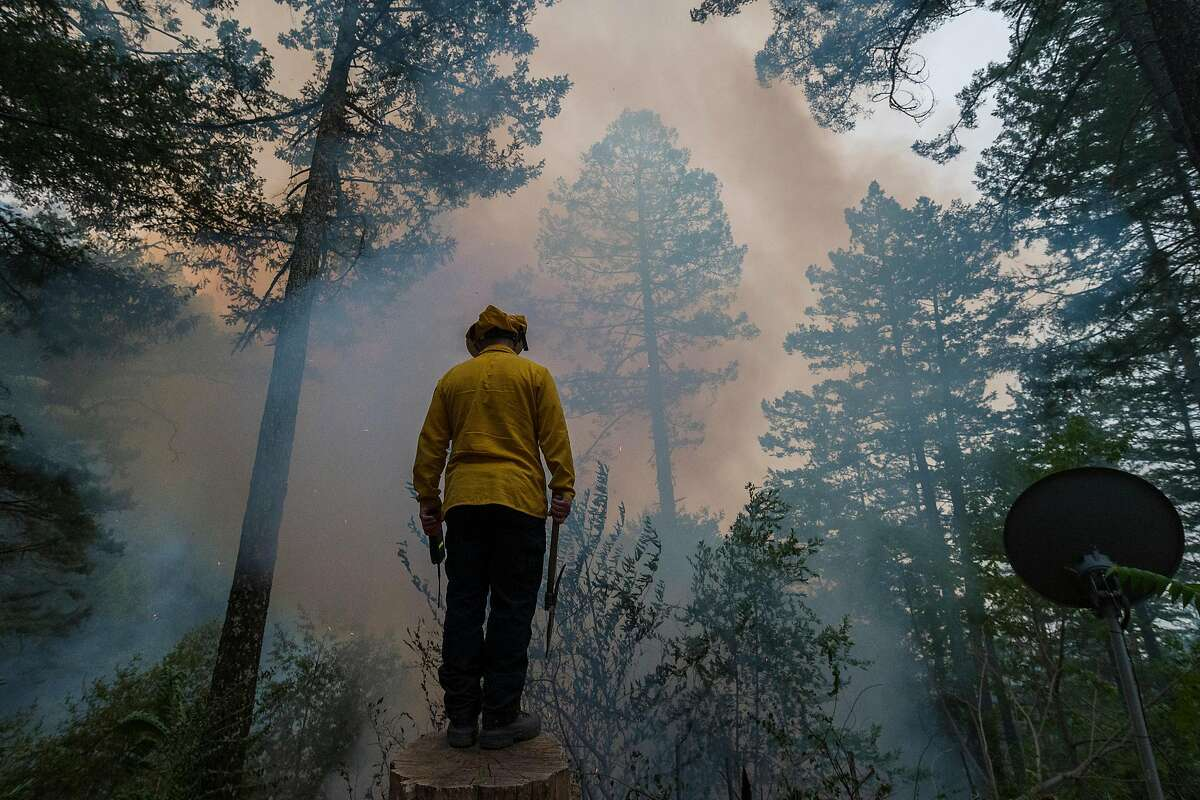 A firefighter watches the Glass Fire burn along Highway 29 near Calistoga, Calif. on Oct. 1, 2020.