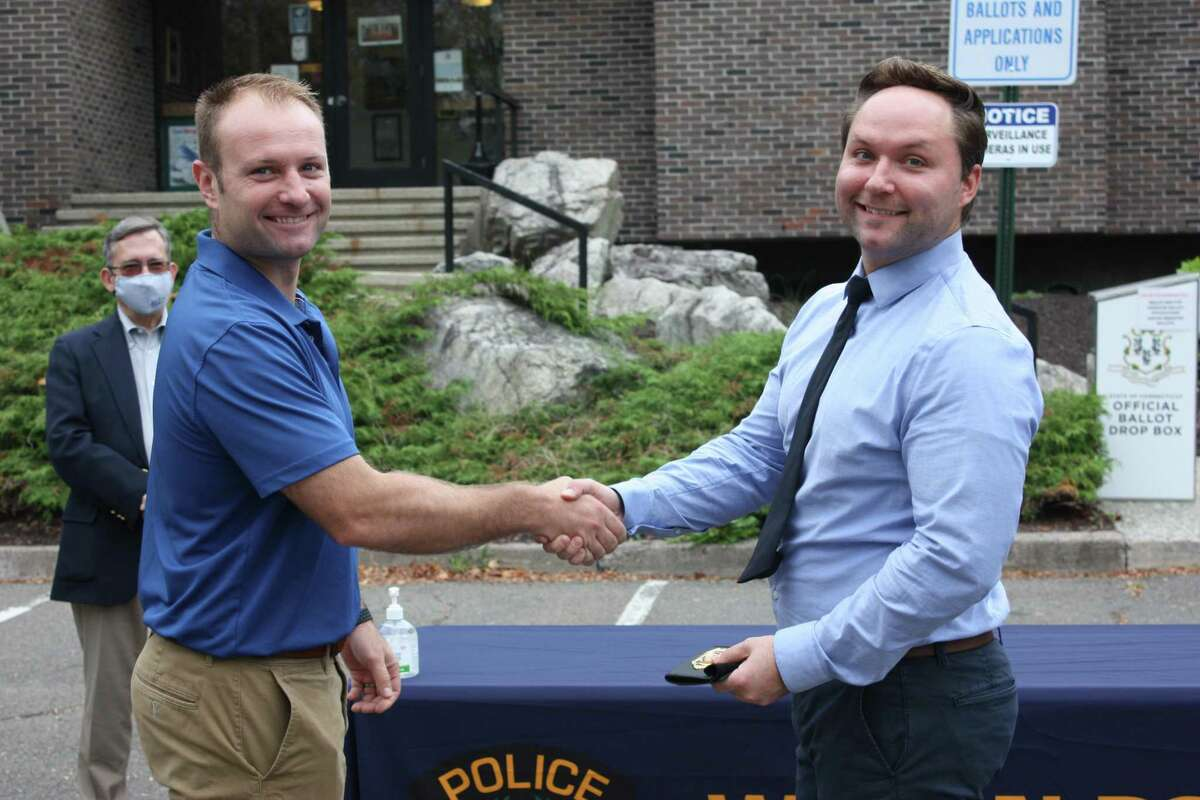 Newly promoted Detective Edward Dolenk, right, receives his badge from his brother, Max Dolenk, who is an officer with the New York City Police Department, during a ceremony at Wilton Police Headquarters on Sept. 29. In the background is Police Commissioner David Waters.