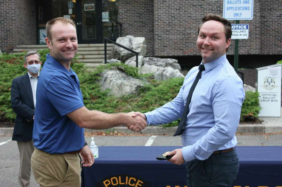 Newly promoted Detective Edward Dolenk, right, receives his badge from his brother, Max Dolenk, who is an officer with the New York City Police Department, during a ceremony at Wilton Police Headquarters on Sept. 29. In the background is Police Commissioner David Waters. Photo: Wilton Police Department / Contributed Photo / Wilton Bulletin Contributed