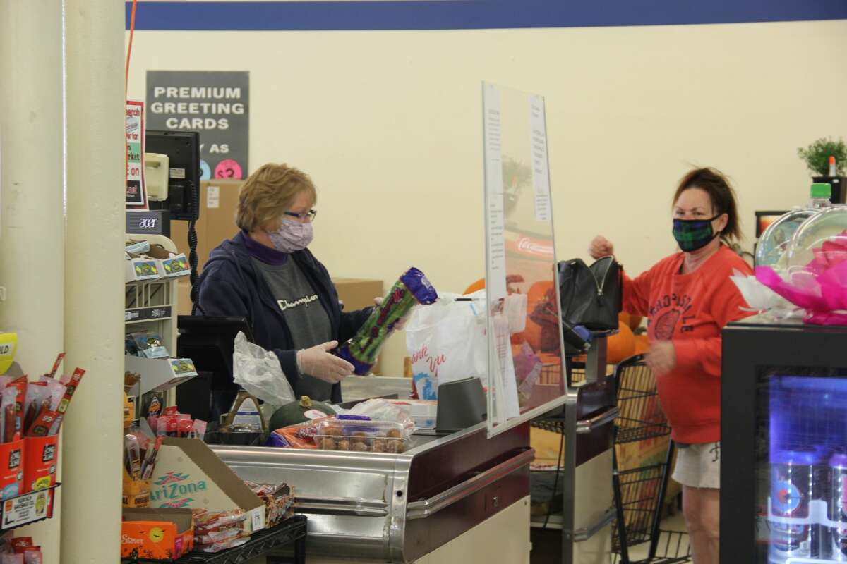 A shopper gets her items checked out at the Pigeon Family Market in Pigeon. The store announced it will be closing its doors at the end of the month.