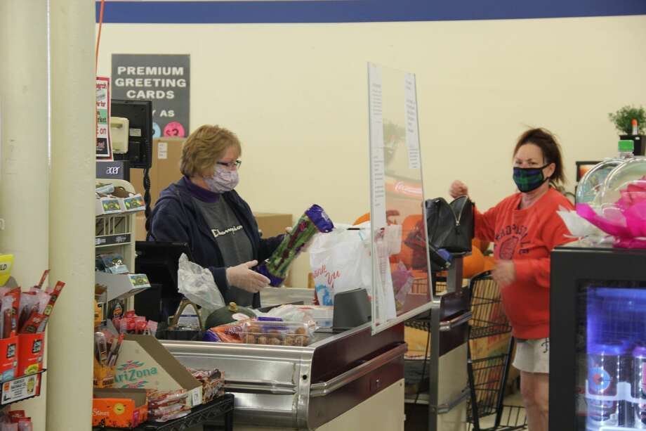 A shopper gets her items checked out at the Pigeon Family Market in Pigeon. The store announced it will be closing its doors at the end of the month. Photo: Robert Creenan/Huron Daily Tribune