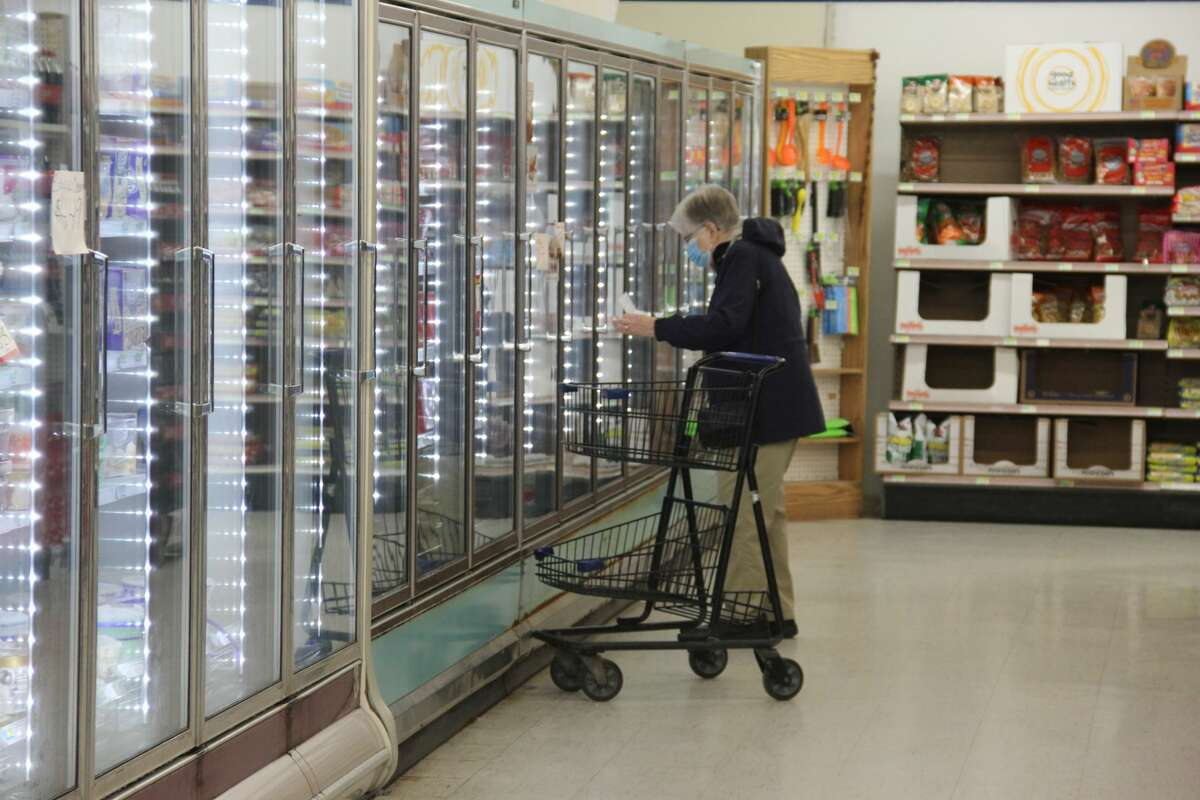 A shopper in the frozen food aisle of the Pigeon Family Market.