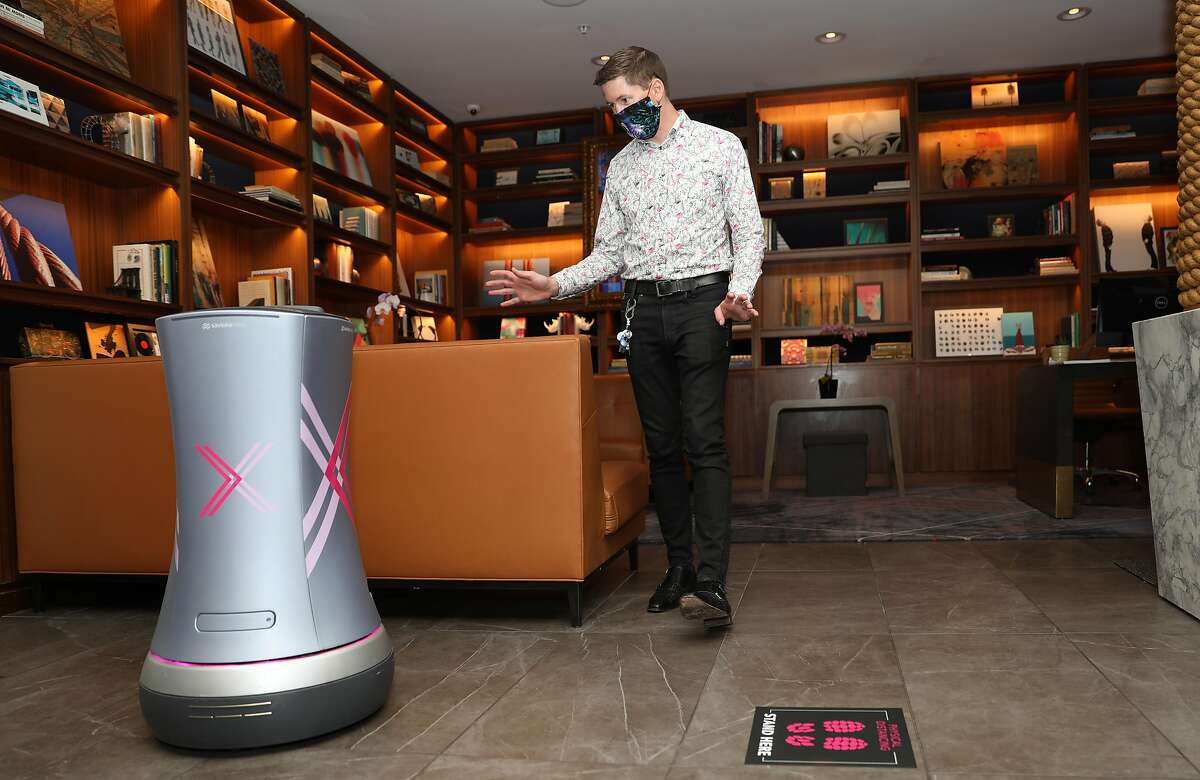 Manager Jeremy Kueffner shows Astro, a room service drone, at the library of the Axiom Hotelseen on Thursday, Oct. 1, 2020, in San Francisco, Calif. More hotels are using these robots during the pandemic to aid the 'touchless' environment hotels.