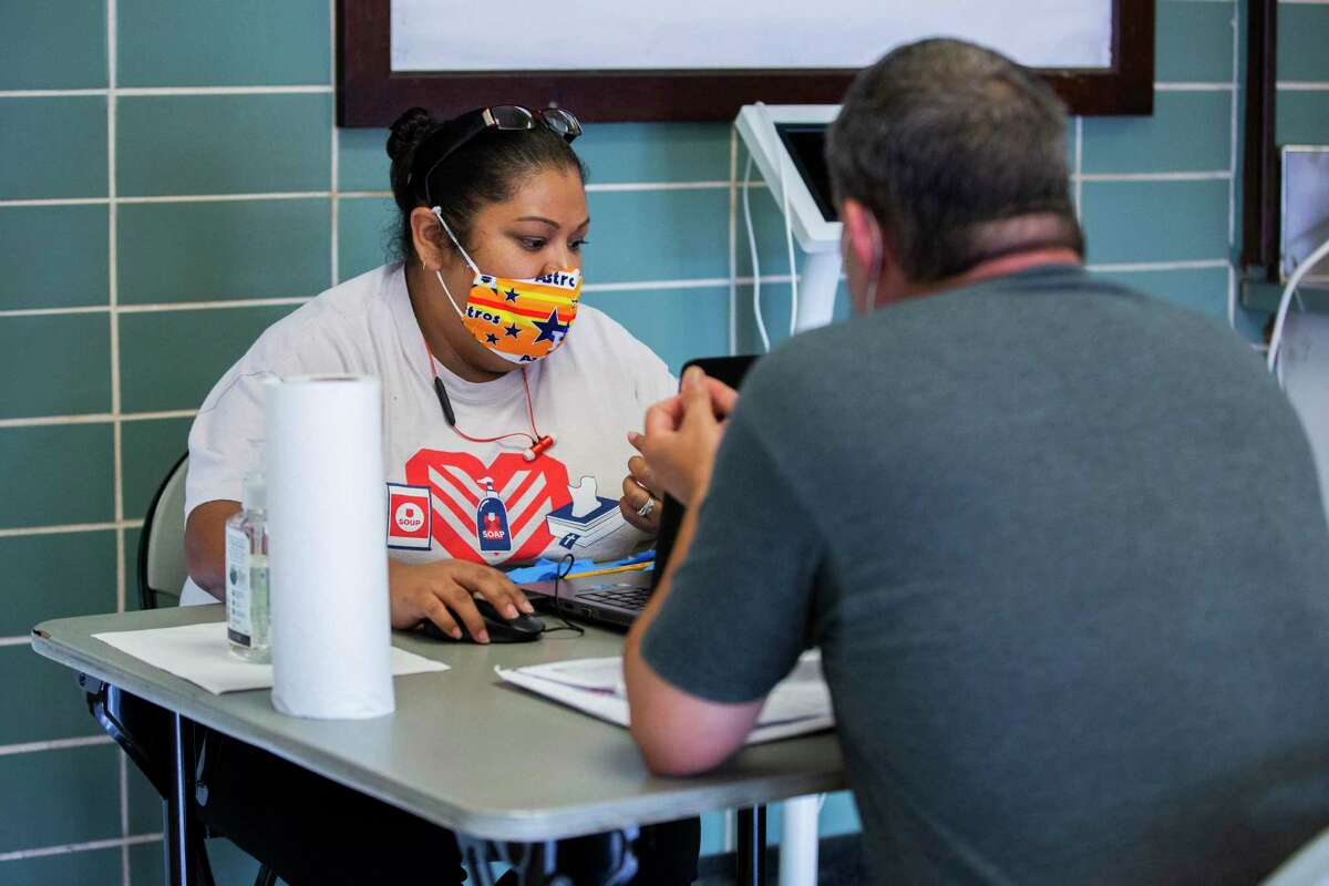 Salvation Army staff member Amanda Herrera makes an assessment to connect a client staying at the moment in a overflow homeless shelter in the Fonde Recreation Center to resources on Tuesday, June 30, 2020, in Houston.