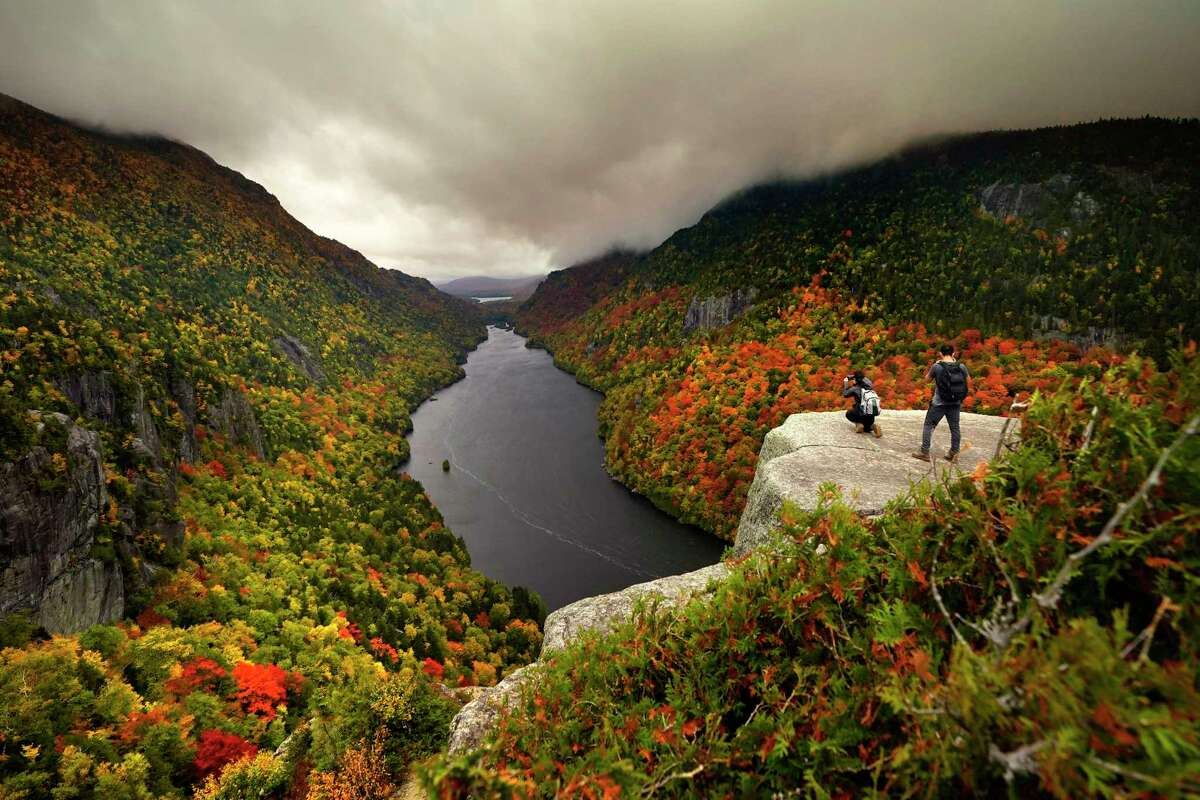 Two visitors photograph the in the colorful autumn view at the Indian Head vista overlooking Lower Ausable Lake in the Adirondacks, Sunday, Sept. 27, 2020, near Keene Valley, N.Y.