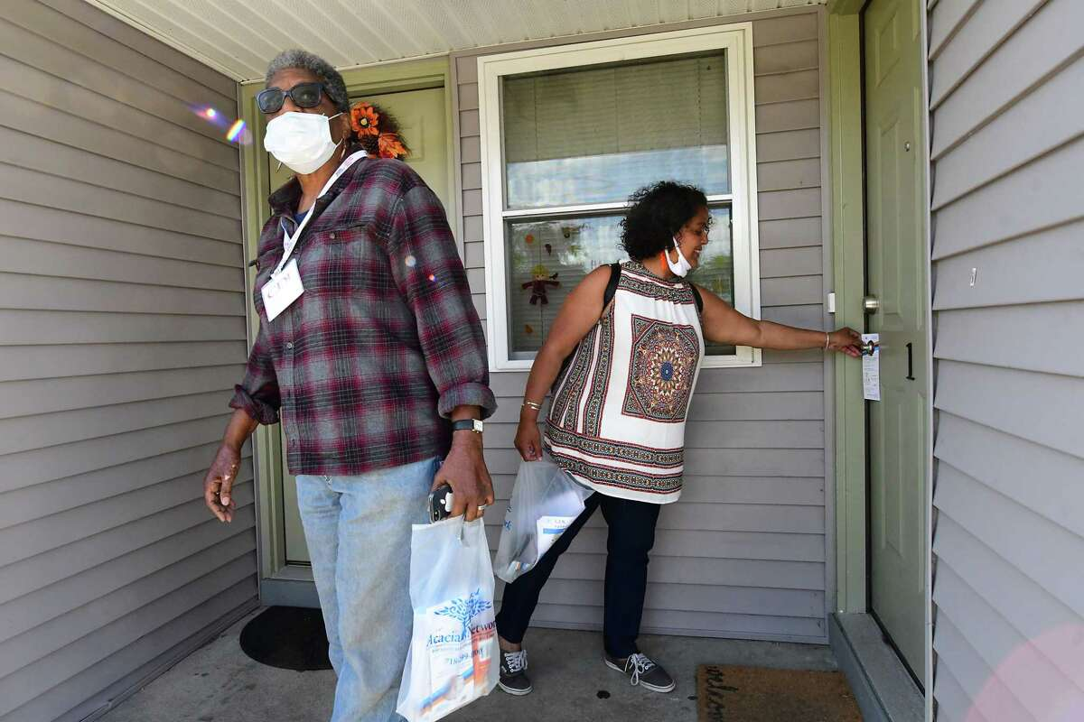 Census outreach workers from Capital District Latinos Cessie Alfonso, left, and Luz Marquez Benbow knock on doors to try and get Arbor Hill residents to complete their census on Wednesday, Sept. 30, 2020 in Albany, N.Y. (Lori Van Buren/Times Union)