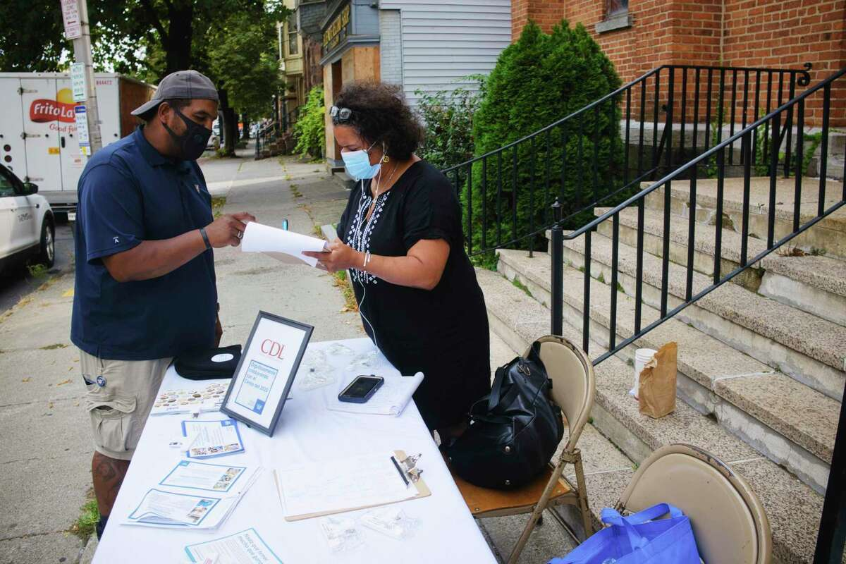 Luz Marquez, right, works with a man to fill out Census information outside the Capital District Latinos offices on Thursday, Sept. 17, 2020, in Albany, N.Y. (Paul Buckowski/Times Union)