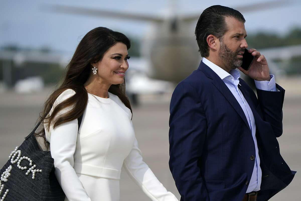 Donald Trump Jr. and Kimberly Guilfoyle walk across the tarmac to board Air Force One at Andrews Air Force Base before flying to Cleveland, Ohio, for the first presidential debate Tuesday, Sept. 29, 2020.