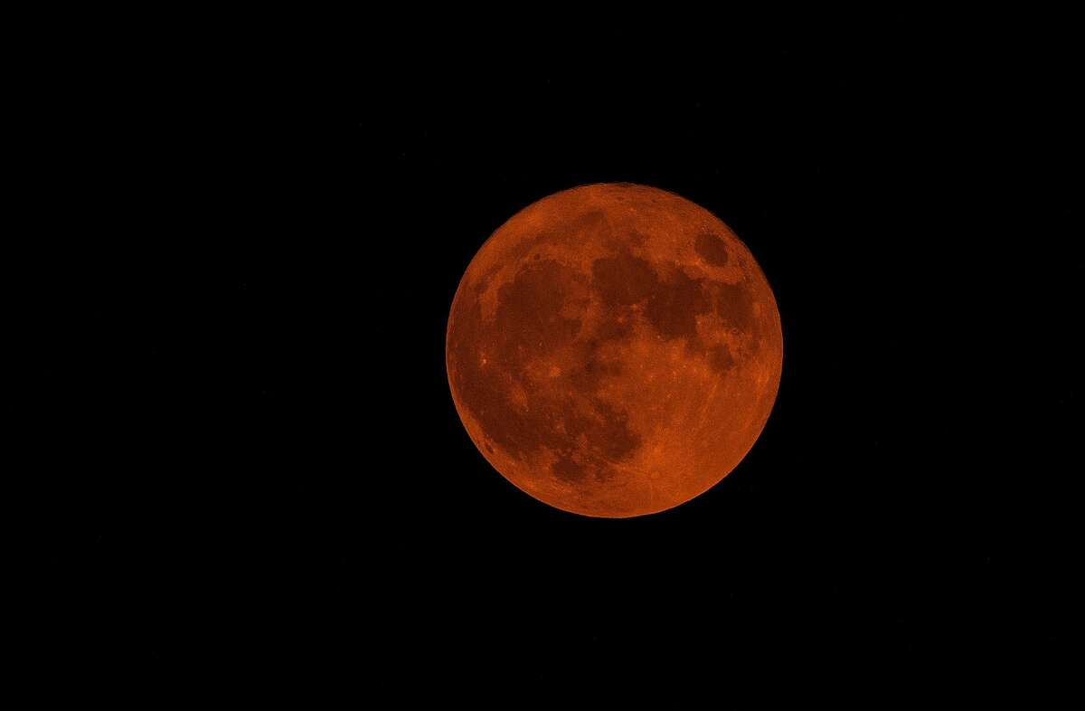 The Harvest Moon for 2020, tinted orange by smoke from the wildfires near the Bay Area, is seen in the sky from Oakland, Calif., on Thursday, October 1, 2020.