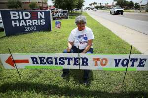 Dora Gonzalez takes a pause in touching up a sign to encourage people to register to vote at the Webb County Democratic Party headquarters in Laredo on Wednesday, Sept. 23, 2020.