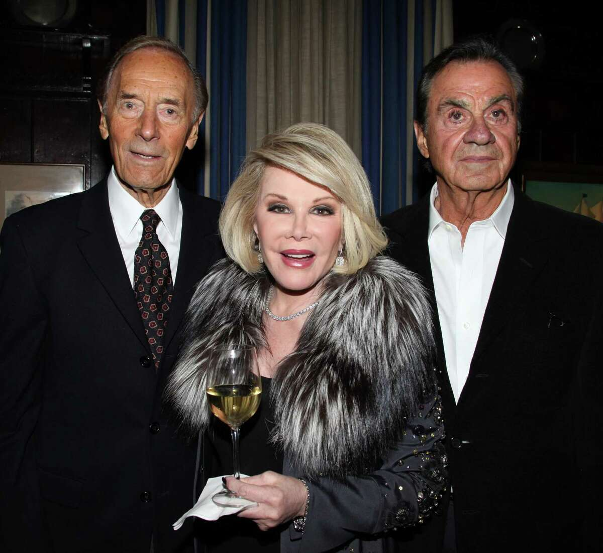 Alan Shayne, left, and his husband Norman Sunshine celebrate with Joan Rivers, who hosted book party for them after an earlier work was published in 2011.
