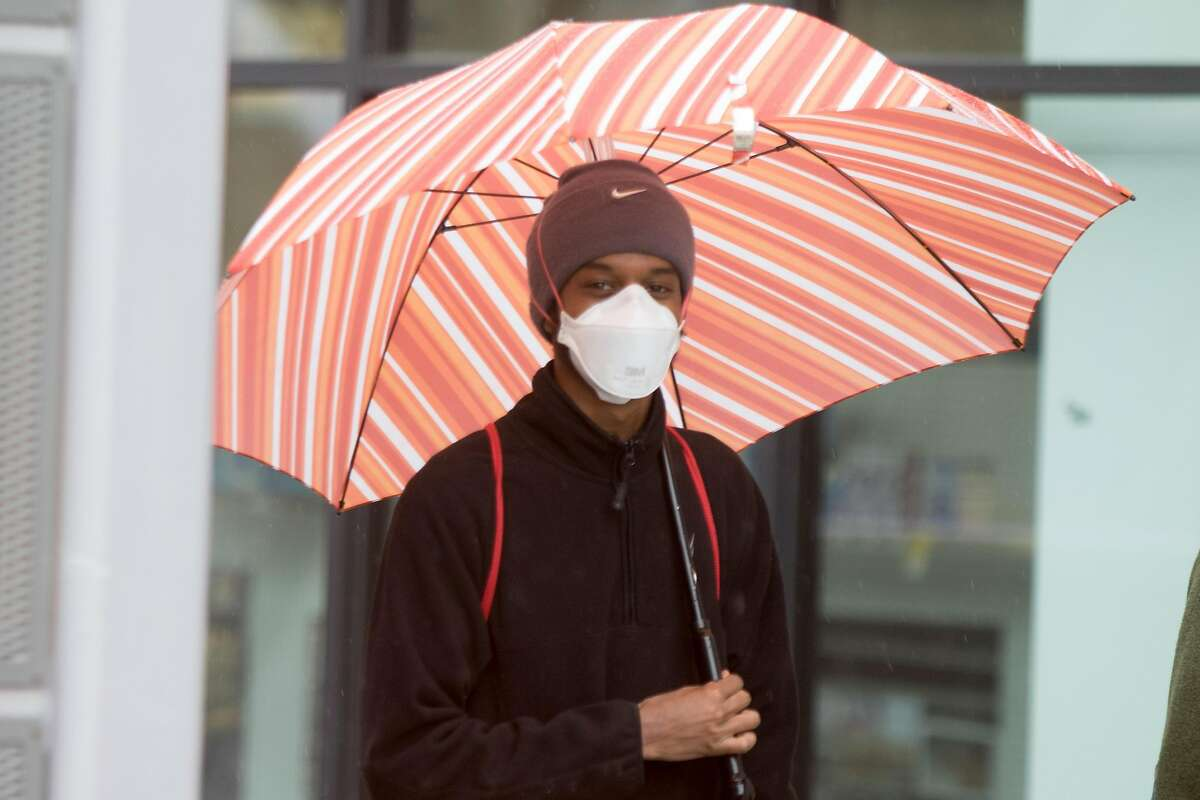 A man wears an N95 mask while holding an umbrella during a rainfall in Berkeley, Calif., on March 25, 2020.