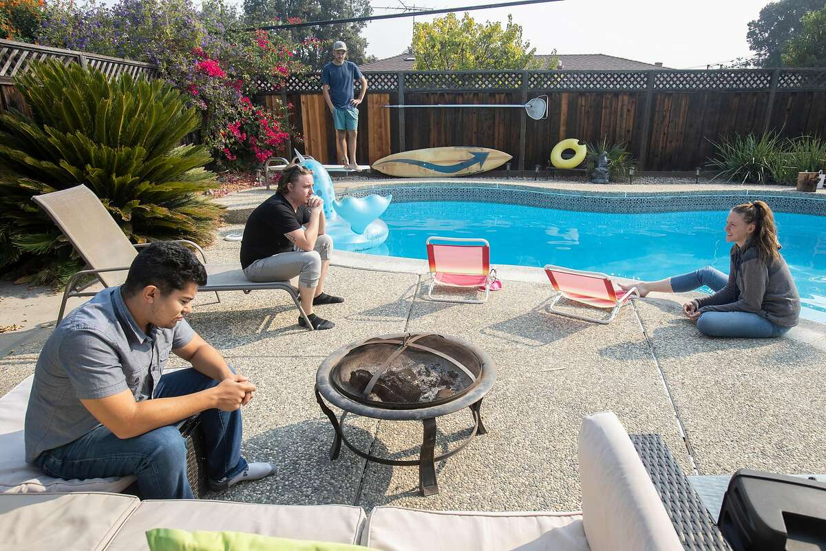 Zack Tobin (left) and his housemates, Adam David, Stone Swiess ,and Michelle Dyslin, in the backyard of their HubHaus corporatized group home on Friday 02 October 2020 in San Jose, CA.