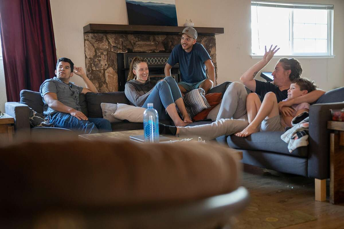 Zack Tobin (left) and his housemates, Michelle Dyslin, Stone Swiess, Adam David and his son Azriel,, in the living room of their HubHaus corporatized group home on Friday 02 October 2020 in San Jose, CA.