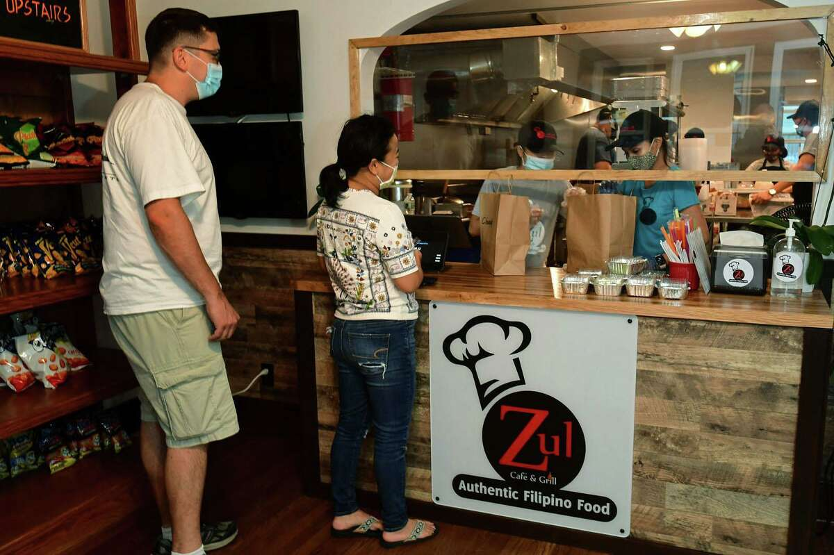 Norwalk residents George Beckwith and Larissa Teodoro pick up their food at Luz Cafe and Grill, an authentic Filipino restaurant, on Thursday in Norwalk. Gladys Luz and her husband opened Zuls in the spring in the midst of a pandemic and they are one of a few restaurants in Norwalk to open while many others close from the financial impact of COVID-19 shutdowns.