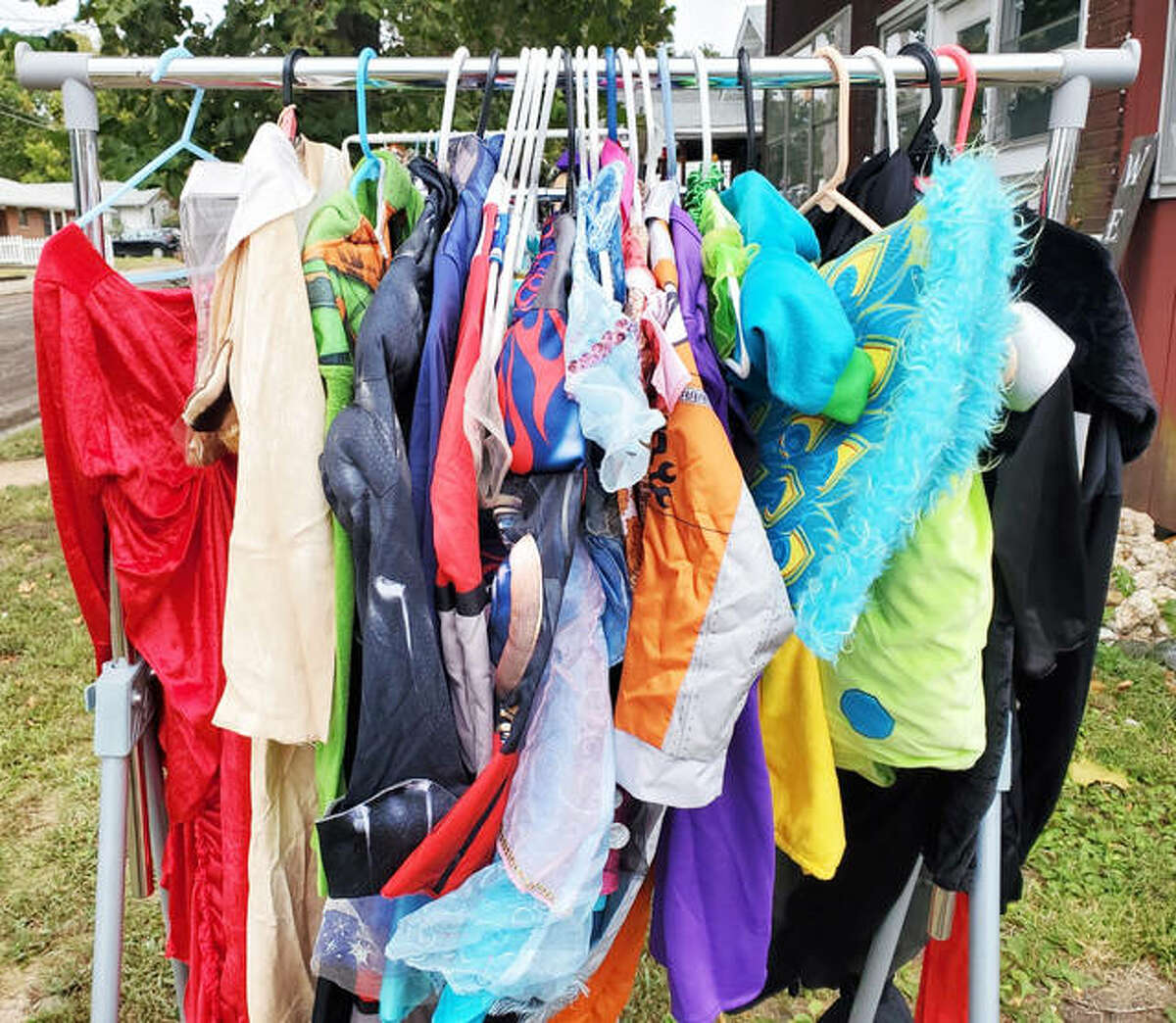 Halloween costumes hang on a rack at Helping Hearts Grow sharing station at 134 Hartnett Ave., Wood River. Visitors can take one costume per child while supplies last. The organization, founded by Rachel Porter-Hunter, also encourages people to bring a costume from last year and hang it on the rack. The no-contact sharing station is open for all.