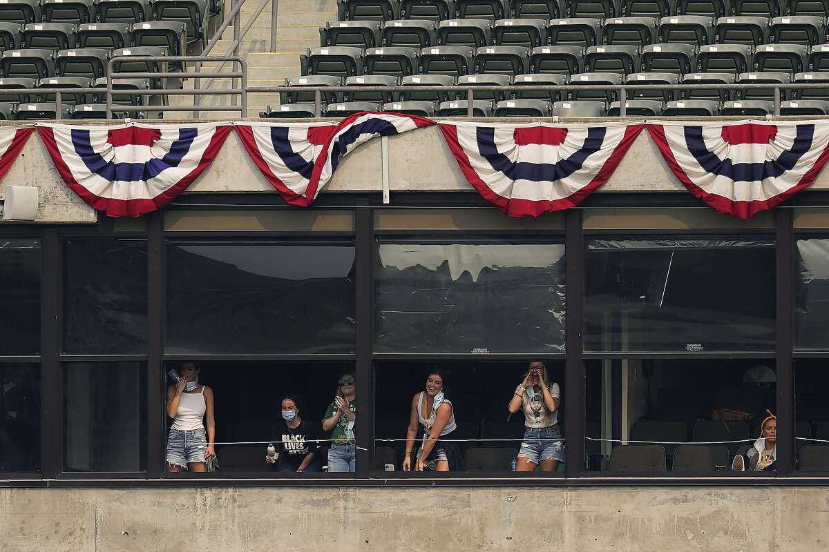 Family of Oakland Athletics players cheer during the fourth inning of Game 3 of an American League wild-card baseball series between the Athletics and the Chicago White Sox, Thursday, Oct. 1, 2020. Left to right: Hannah Maserjian, Kristi Hendriks, Jenna McFarland, Amanda Diekman, Amanda Sedley. (AP Photo/Eric Risberg)