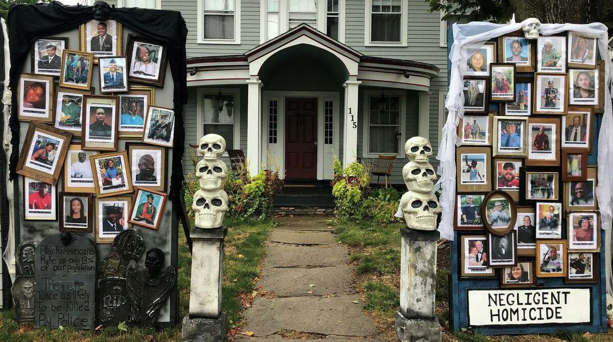 """The """"Halloween House"""" on Main Street in West Hartford, Conn. The Warshauer family, who live in the house, used this year's display to focus on the COVID-19 pandemic and the Black Lives Matter movement. """"In 2003 with the American invasion of Iraq, I felt like I needed to make a statement,"""" he said. That year, he created an effigy of then-President George W. Bush and then-Vice President Dick Cheney, both wearing pants covered in flames, next to a sign that read """"liar, liar, pants on fire."""""""