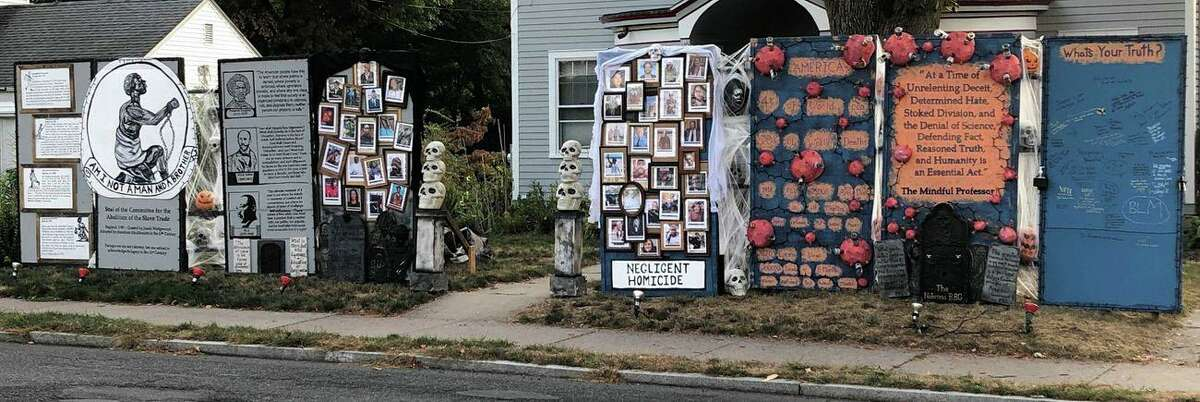 """The """"Halloween House"""" on Main Street in West Hartford, Conn. The Warshauer family, who live in the house, used this year's display to focus on the COVID-19 pandemic and the Black Lives Matter movement. Over the years, local residents have come to know Warshauer's home as the """"Halloween House"""" as thousands pass by each day on the busy West Hartford street. Warshauer, a history professor at Central Connecticut State University, said this year's display and the one in 2003 were his response to """"gigantic lies ... whether it's lying to send us to war or lying about the legacy of systemic racism ... and the COVID-19 pandemic."""""""