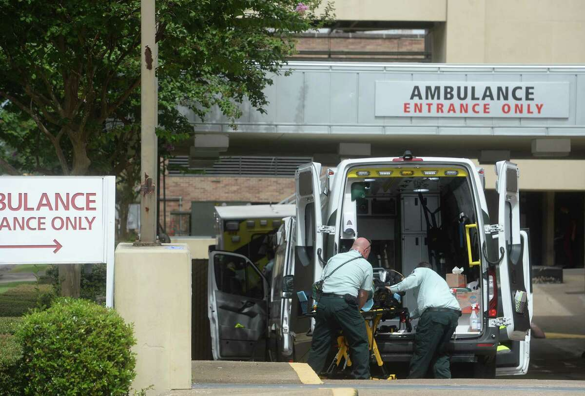 Ambulances are parked in the Emergency Room drive at Christus St. Elizabeth Hospital in Beaumont Tuesday, where crews clean and wait after making patient deliveries. Photo taken Tuesday, July 21, 2020 Kim Brent/The Enterprise
