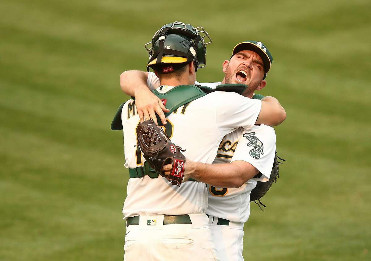 OAKLAND, CALIFORNIA - OCTOBER 01: Liam Hendriks #16 of the Oakland Athletics celebrates with Sean Murphy #12 after they beat the Chicago White Sox 6-4 in Game Three of the American League wild card series at RingCentral Coliseum on October 01, 2020 in Oakland, California. (Photo by Ezra Shaw/Getty Images) *** BESTPIX ***