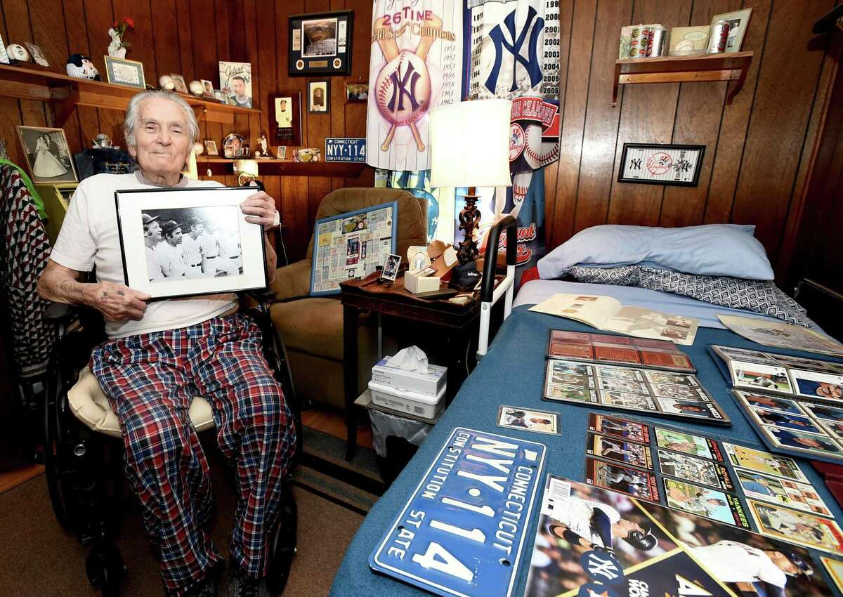 Ernest Grande, 86, holding a photograph of New York Yankees baseball players Mickey Mantle, Yogi Berra, Whitey Ford, Joe DiMaggio and Casey Stengel as he sits on Oct. 01, 2020, with a small part of his extensive collection of New York Yankees memorabilia that he has been collecting since the 1960s.