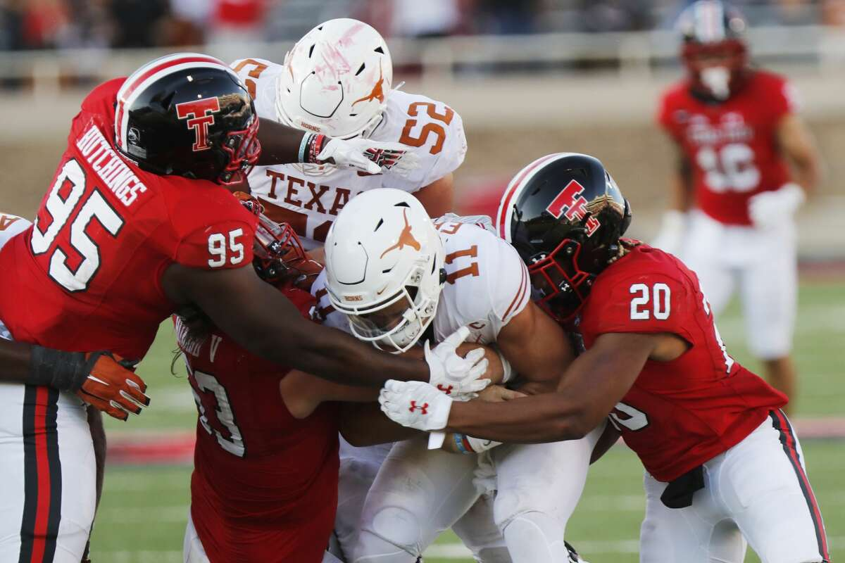 Texas Tech defensive lineman Jaylon Hutchings and linebacker Kosi Eldridge tackle Texas quarterback Sam Ehlinger during the second half of an NCAA college football game against Texas Tech, Saturday Sept. 26, 2020, in Lubbock. (AP Photo/Mark Rogers)