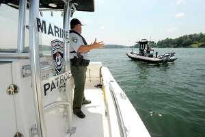 Assistant Chief Ron Barnard of the Candlewood Lake Authority Marine Patrol, talks to Steve Cammack, with the state Department of Energy and Environmental Protection police on Candlewood Lake in 2018.