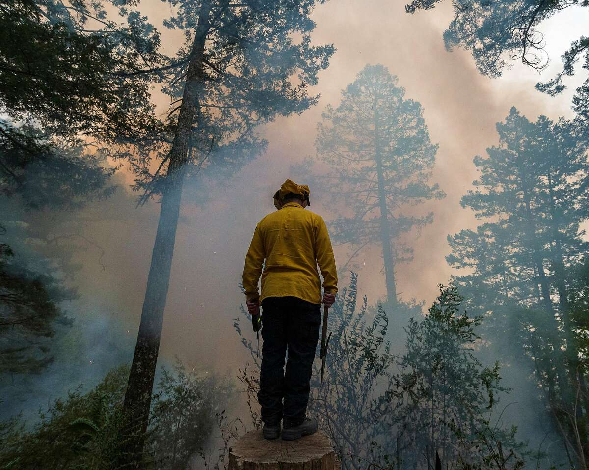 A firefighter monitors the Glass Fire along Highway 29 near Calistoga. The fire has consumed more than 60,000 acres.