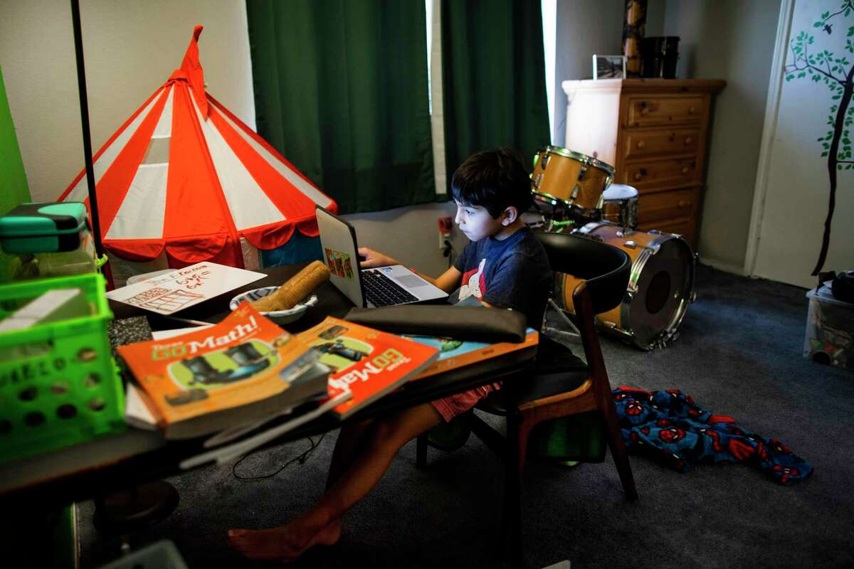 Parker Elementary School second-grader Laurenzo Garza, 7, works on language arts material during online classes in his bedroom Friday. Laurenzo's mother, Adela Justice, plans to keep him in virtual classes for Houston ISD's second grading period, an option that more than half of the district's nearly 200,000 students might choose this fall.