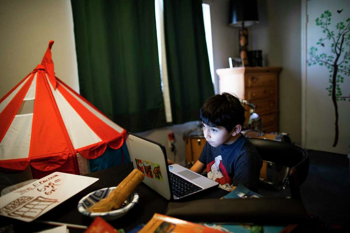 Parker Elementary School second-grader Laurenzo Garza, 7, works on language arts material during online classes in his bedroom Friday. Laurenzo says he enjoys studying at home and spending more time with his mother, Adela Justice, who works from their home on Houston's southwest side.