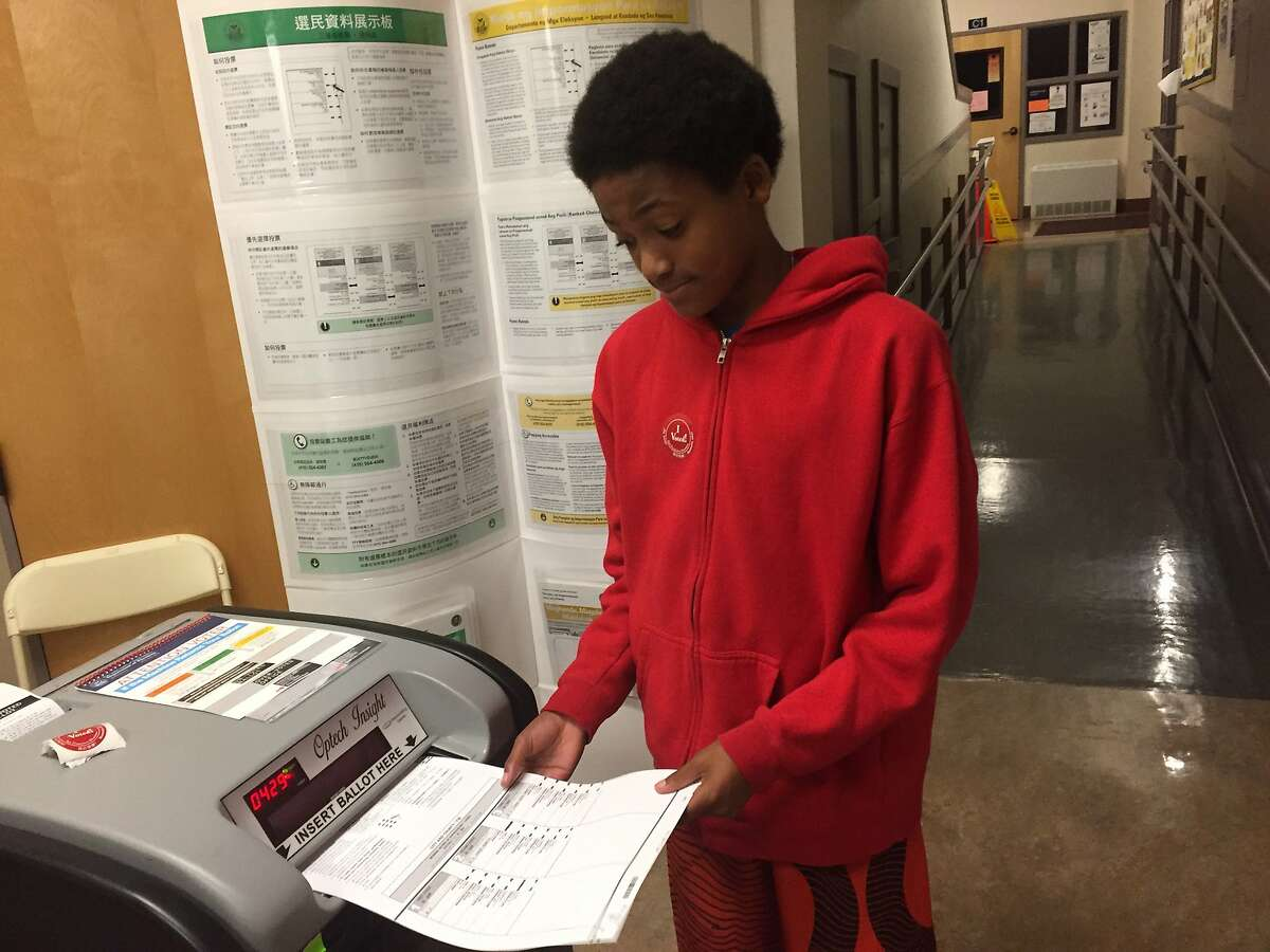 Zane Fisher-Paulson turns a ballot in for his parents in November 2016.