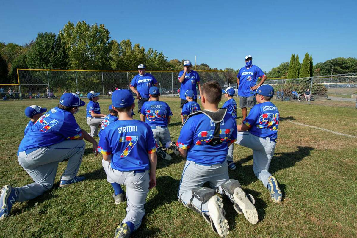 Players and coaches of the North Colonie Bison 11U team, all sporting jerseys with colored puzzle pieces, the symbol for autism, fashioning their numbers and trim prior to a game against Guilderland at the Boght Road Baseball complex in Colonie, NY, on Saturday, Sept. 26, 2020 (Jim Franco/special to the Times Union.)