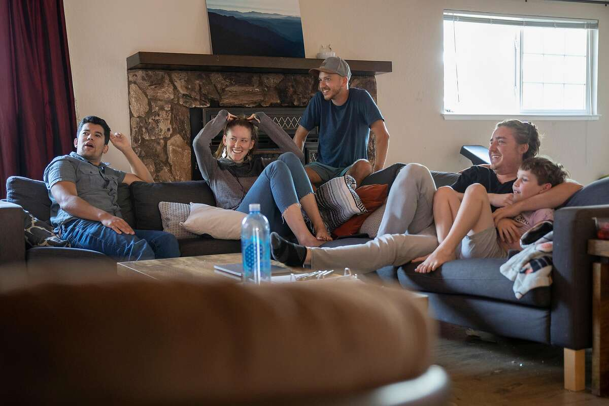 Zack Tobin (left) and his housemates, Michelle Dyslin, Stone Swiess, Adam David and his son Azriel, in the living room of their HubHaus corporatized group home on Friday 02 October 2020 in San Jose, CA.