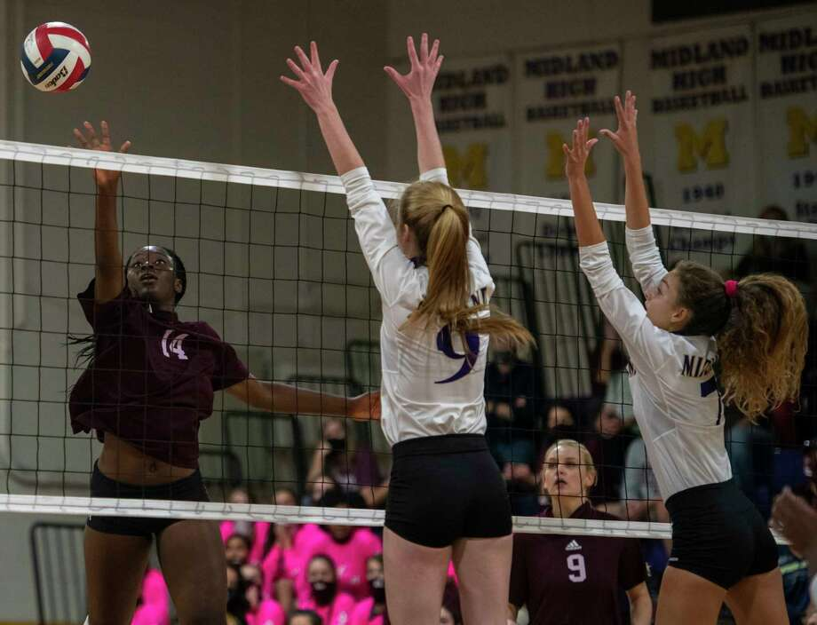 Lee's Loredana Fouonji (14) tips the ball around Midland High's Madelyn Kennedy (9) and Olivia Hale (7) on Friday, Oct. 2, 2020 at Midland High School. Jacy Lewis/Reporter-Telegram Photo: Jacy Lewis/Reporter-Telegram / MRT