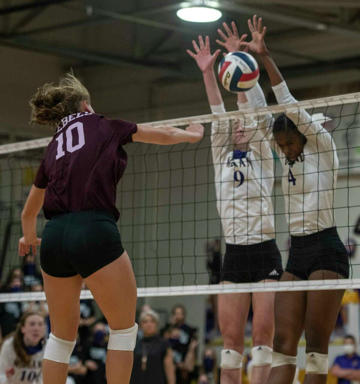 Lee?•s Brylee Awbrey (10) hits the ball into Midland High?•s Madelyn Kennedy (9) and Aniya Clinton (4) block Friday, Oct. 2, 2020 at Midland High School. Jacy Lewis/Reporter-Telegram