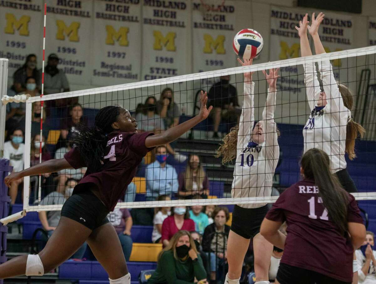 Lee's Loredana Fouonji (14) tips the ball past the blockattempt of Midland High's Ella Gideon (10) and Grace Utter (20)Friday, Oct. 2, 2020 at Midland High School. Jacy Lewis/Reporter-Telegram