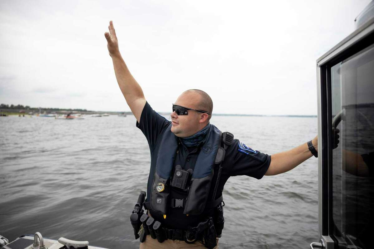 Lt. Miguel Rosario waves back at visitors as he patrols Lake Conroe, Saturday, Sept. 5, 2020. Due to the COVID-19 pandemic the 21,000-acre lake saw seen a huge increase in visitors after most businesses were forced to shut down.