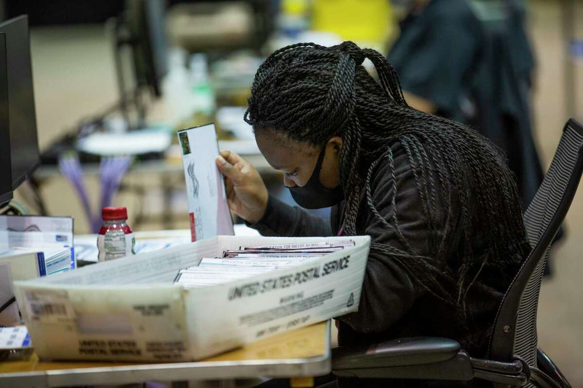A Harris County worker sorts mail-in ballots applications at the Harris County Clerk's election headquarters at the NRG Arena on Friday, Sept. 25, 2020, in Houston.