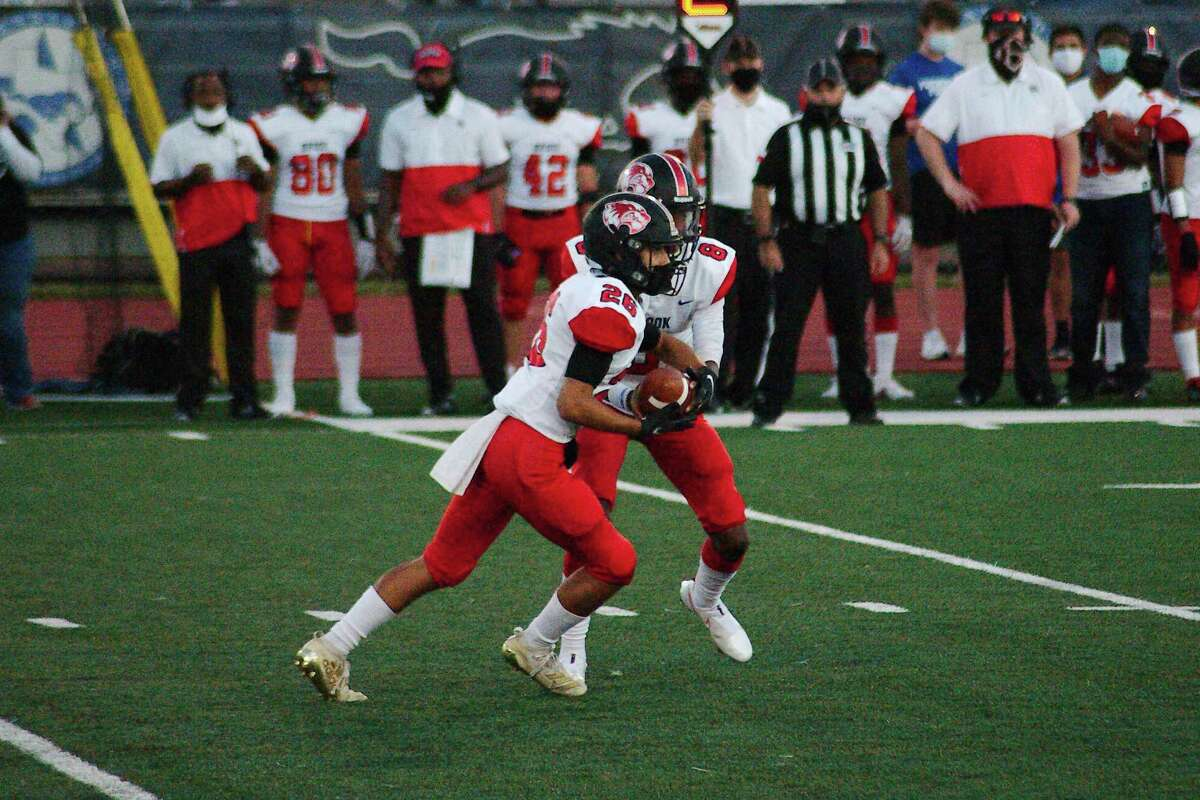 Clear Brook's Adrian Castillo (26) takes the handoff from Clear Brook's Cameron McCalister (8) against Friendswood Friday Oct. 2 at Friendswood High School.