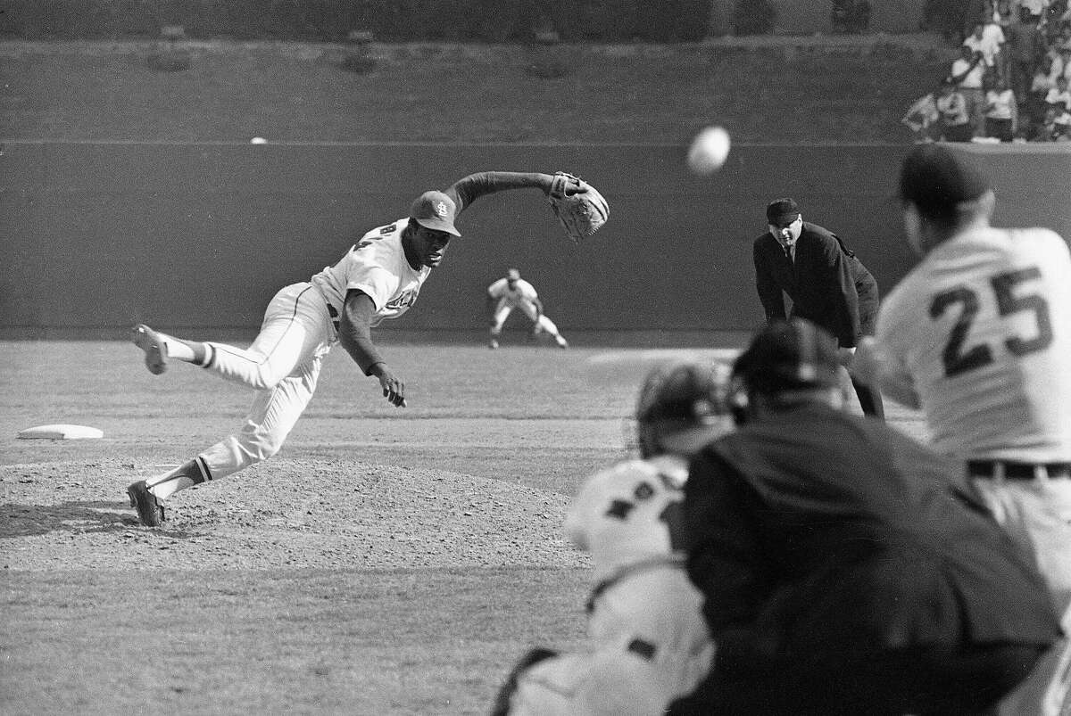 Bob Gibson throws a pitch to Detroit's Norm Cash in the ninth inning of St. Louis' 4-0 win in Game 1 of the 1968 World Series. Gibson, who won a record seven consecutive World Series starts, died Friday. He was 84.