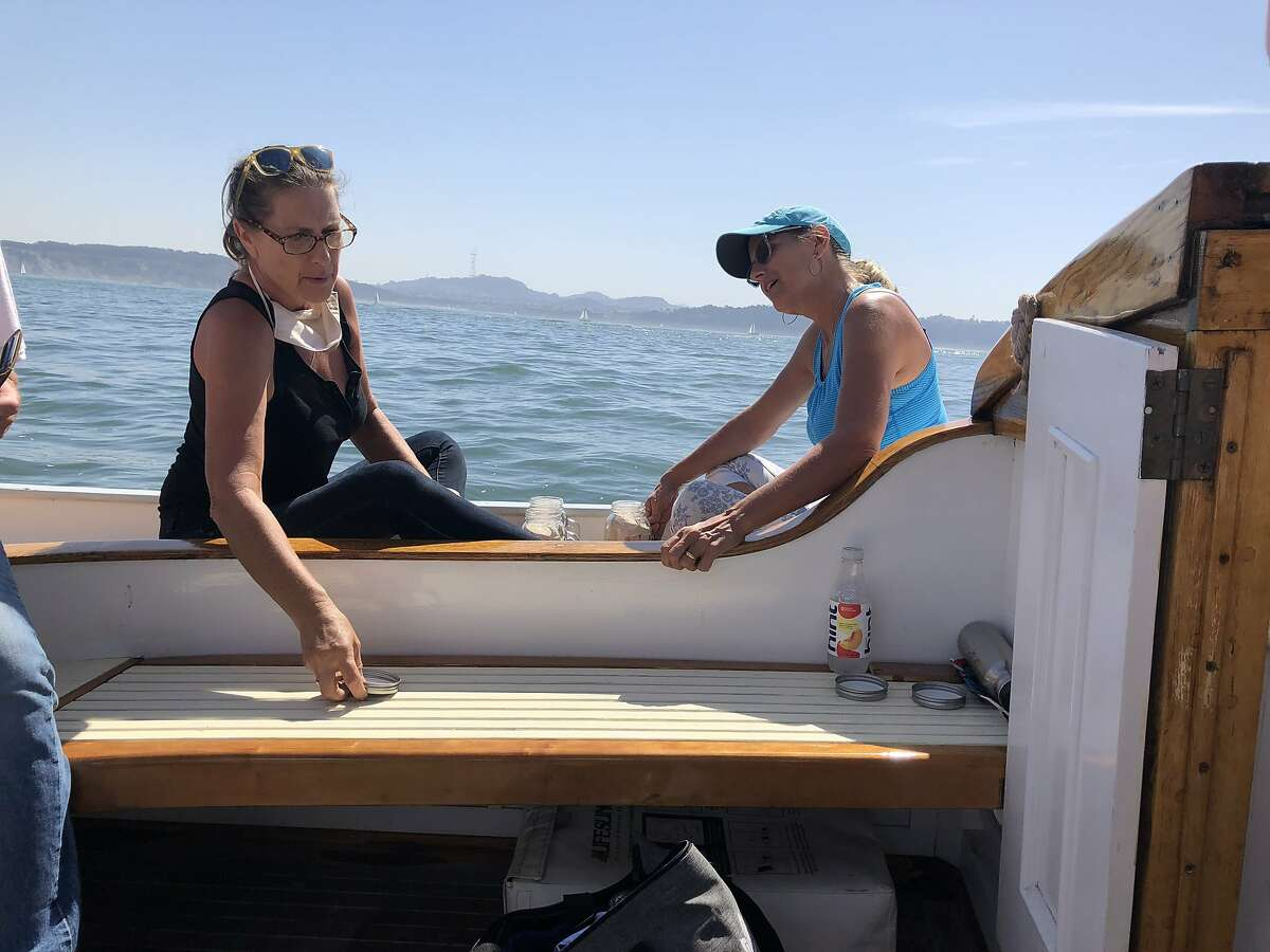 Berit (left) and Inga Larsen prepare to cast the ashes of their father, David Lar sen, out side the Golden Gate. Robert Copeland's ashes also went over the side.