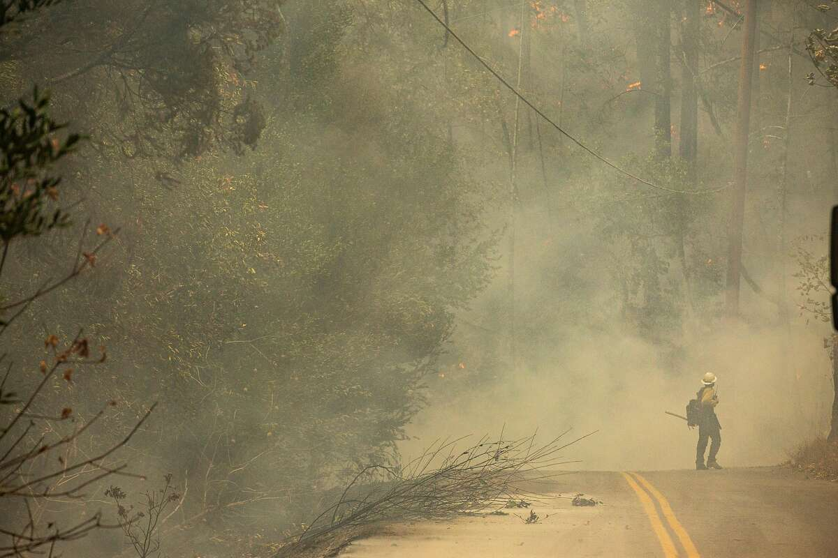 A firefighter with a shovel along Spring Mountain Road monitors the Glass Fire that's burning up a hill and moving towards the Charbay Winery, Friday, Oct. 2, 2020, in St. Helena, Calif.
