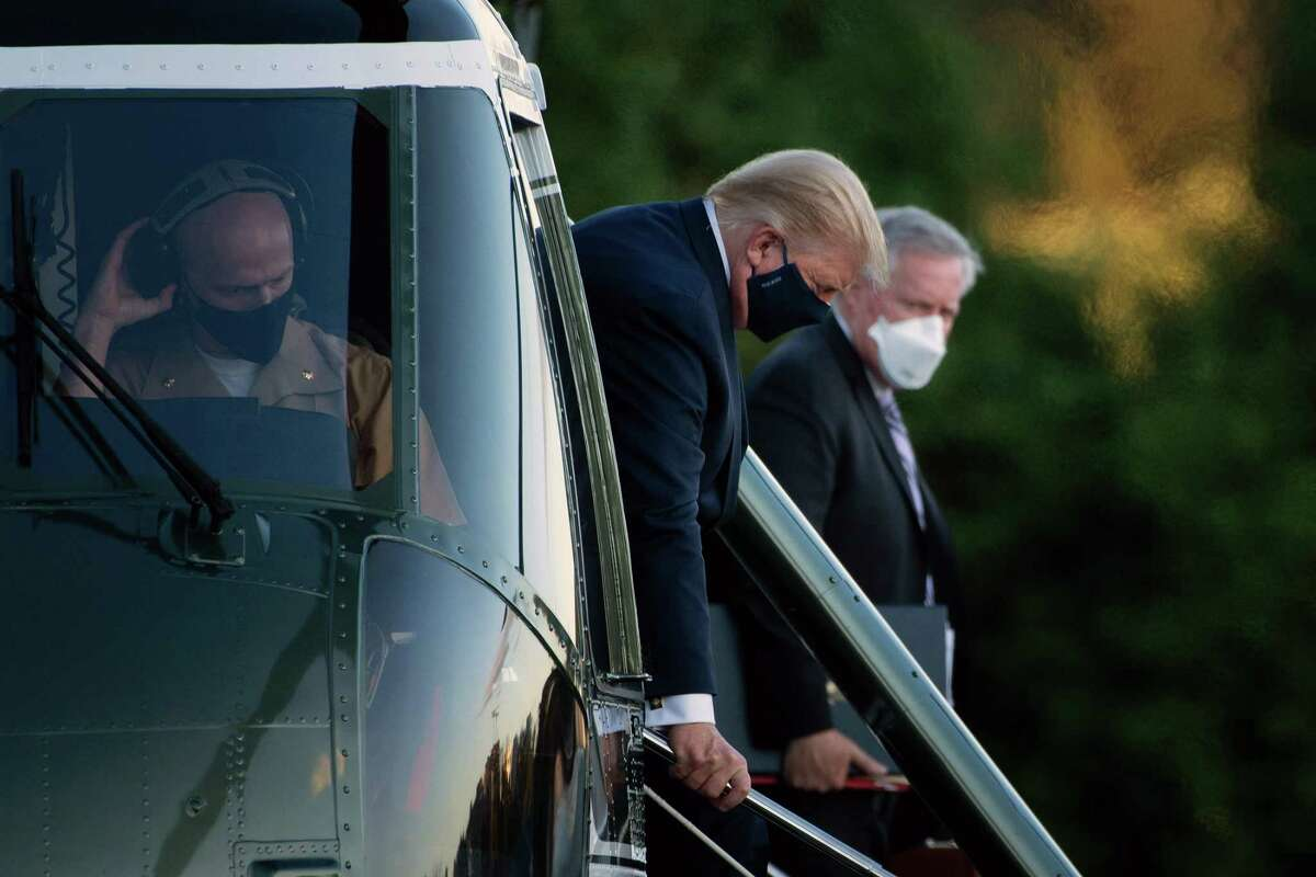 TOPSHOT - White House Chief of Staff Mark Meadows (R) watches as US President Donald Trump walks off Marine One while arriving at Walter Reed Medical Center in Bethesda, Maryland on October 2, 2020, after testing positive for covid-19. - President Donald Trump will spend the coming days in a military hospital just outside Washington to undergo treatment for the coronavirus, but will continue to work, the White House said Friday (Photo by Brendan Smialowski / AFP) (Photo by BRENDAN SMIALOWSKI/AFP via Getty Images)