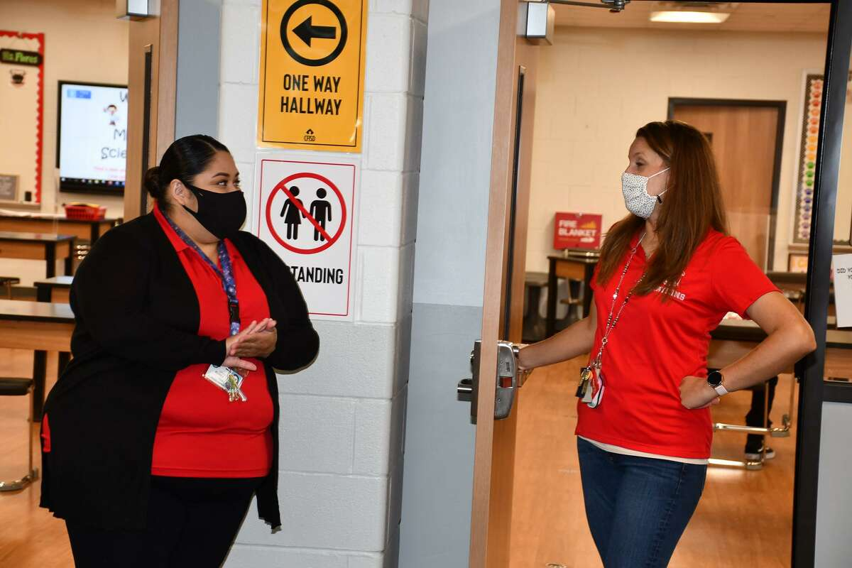 Signs with health and safety protocols are displayed in a hallway at Watkins Middle School in Cy-Fair ISD.