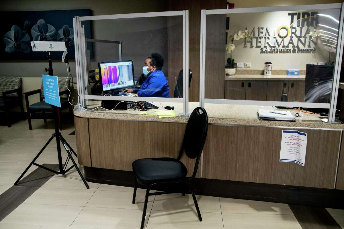 The front reception desk, with a thermal scanner being used is shown at TIRR Memorial Hermann is shown on Thursday, July 23, 2020 in Houston.